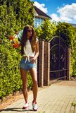 Fille élégante dans des poses de lunettes de soleil avec le longboard Photographie stock