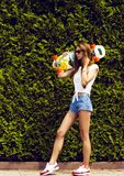 Fille élégante dans des poses de lunettes de soleil avec le longboard photographie stock libre de droits