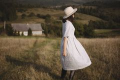 Fille élégante dans la robe et le chapeau de toile marchant dans l'herbe ensoleillée de champ au village en montagnes Femme de Bo photo stock