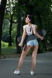 Fille élégante de brune avec des shorts en verre, prises une planche à roulettes, a Images stock