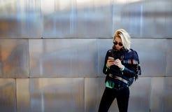 Fille élégante de hippie causant au téléphone de cellules tout en se tenant sur le fond métallique urbain photographie stock