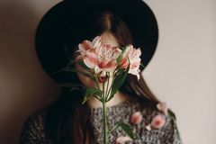 Fille élégante de hippie dans le chapeau tenant les fleurs et les pétales roses sur s Photographie stock libre de droits