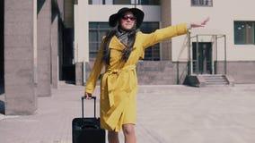 Fille élégante en chapeau jaune et verres d'imperméable avec des crochets de bagage un taxi clips vidéos