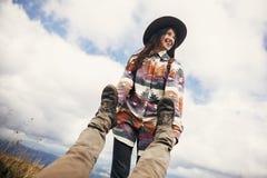 Fille élégante heureuse de voyageur dans le chapeau tenant des jambes d'homme, traction Photographie stock libre de droits