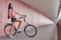Fille élégante sexy de brune portant des caleçons d'une chemise rose et de denim de flanelle en verres, posant avec le vélo de vi Photos stock