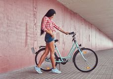 Fille élégante sexy de brune portant des caleçons d'une chemise rose et de denim de flanelle en verres, posant avec le vélo de vi Image stock