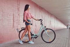Fille élégante sexy de brune portant des caleçons d'une chemise rose et de denim de flanelle en verres, posant avec le vélo de vi Image libre de droits