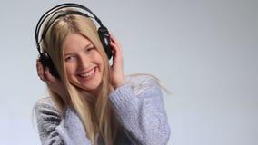 Fille émotive appréciant la musique dans des écouteurs banque de vidéos