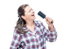 Fille émotive dans des pyjamas chantant dans la brosse à cheveux sur le blanc Photo libre de droits