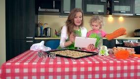 Fille émotive de mère et de fille étudiant des recettes de bonbons sur la tablette clips vidéos