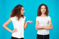 Fille étant offensée par à sa jumelle de soeur dans des écouteurs au-dessus de fond bleu Photographie stock