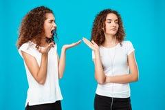 Fille étant offensée par à sa jumelle de soeur dans des écouteurs au-dessus de fond bleu Image stock