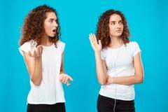 Fille étant offensée par à sa jumelle de soeur dans des écouteurs au-dessus de fond bleu Photo stock