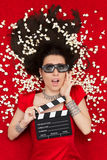 Fille étonnée avec des verres du cinéma 3D, directeur Clapboard de maïs éclaté Photographie stock