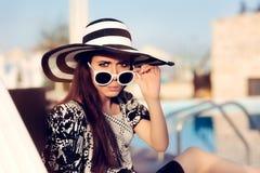 Fille étonnée avec les lunettes de soleil et le chapeau se reposant sur la chaise de Sun photos stock