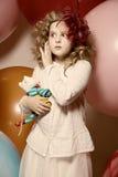 Fille étonnée avec un jouet mou entouré par les ballons énormes Images libres de droits