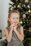 Fille étonnée avec une étoile dans un arbre de Noël Photos stock