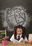 Fille étonnée d'étudiant à la lecture de table contre le tableau noir gris avec l'école et le graphique d'éducation Photographie stock
