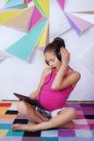Fille étonnée d'enfant avec un comprimé dans la chambre Le concept de images stock