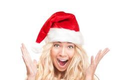 Fille étonnée dans le chapeau rouge de Santa d'isolement sur le blanc. Images stock
