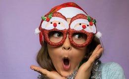 Fille étonnée en chapeau et verres de Santa s Photographie stock libre de droits