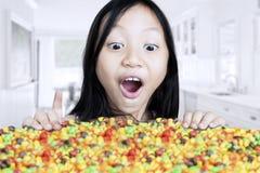 Fille étonnée regardant des sucreries à la maison Photos libres de droits
