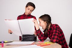 Fille étonnée regardant le carnet ouvert de l'enfant indifférent l'école photographie stock libre de droits