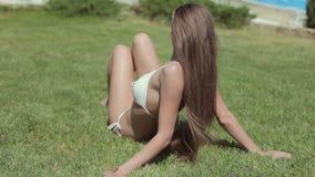 Fille étonnante dans un bikini blanc se trouvant sur l'herbe banque de vidéos