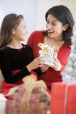 Fille étonnante sa mère avec le cadeau de Noël Photographie stock libre de droits