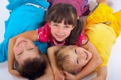Fille étreignant deux amis heureux Photographie stock libre de droits