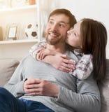 Fille étreignant et embrassant le papa dans la joue Photos libres de droits