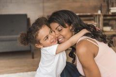 Fille étreignant la mère de sourire tout en passant le temps à la maison Photos libres de droits