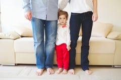 Fille étreignant la maman et le papa pour des jambes photographie stock libre de droits