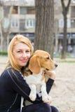 Fille étreignant le chien de briquet en parc Photographie stock