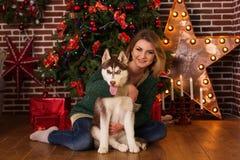 Fille étreignant le chien enroué près de l'arbre de Noël Photographie stock libre de droits