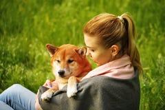 Fille étreignant le chien Shiba Inu Image stock