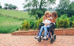 Fille étreignant sa mère supérieure dans le fauteuil roulant Photos stock