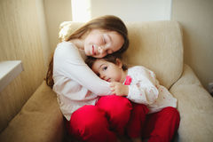Fille étreignant sa plus jeune soeur photographie stock