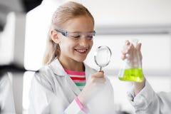 Fille étudiant le tube à essai au laboratoire d'école image libre de droits