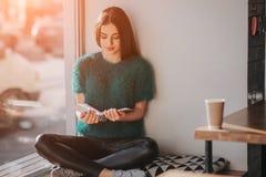 Fille absorbée dans le livre de lecture pendant la coupure en café Beau livre de lecture mignon de jeune femme et café potable Image stock