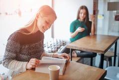 Fille absorbée dans le livre de lecture pendant la coupure en café Beau livre de lecture mignon de jeune femme et café potable Photos stock