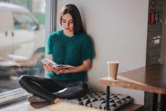 Fille absorbée dans le livre de lecture pendant la coupure en café Beau livre de lecture mignon de jeune femme et café potable Photo stock