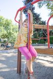 Fille accrochant sur la barre dans l'observation de terrain de jeu et de mère Photo stock