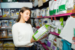 Fille achetant la nourriture sèche pour des animaux familiers dans la boutique Images stock
