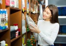 Fille achetant la nourriture sèche pour des animaux familiers dans la boutique Photos libres de droits