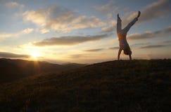 Fille acrobatique sur le coucher du soleil photos stock