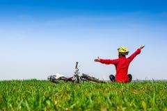 Fille active heureuse avec la bicyclette appréciant la vue sur un pré vert photos stock