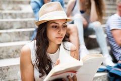 Fille adolescente d'étudiant s'asseyant sur les étapes en pierre lisant un livre Images libres de droits