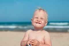 Fille adorable à la plage appliquant la crème de sunblock images libres de droits
