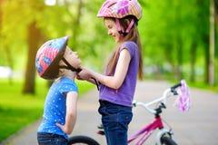 Fille adorable aidant sa soeur à mettre un casque de bicyclette dessus Images stock